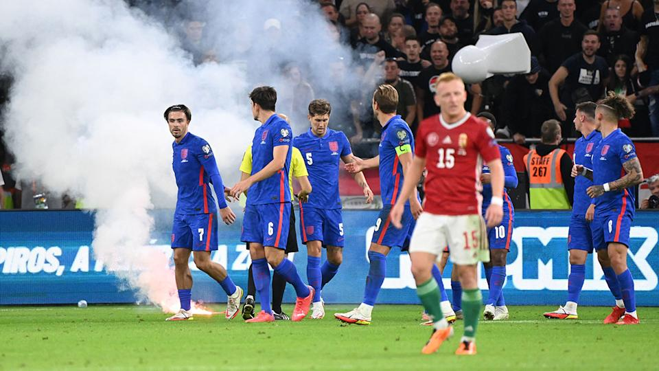 England players, pictured here being pelted with cups and allegedly racially abused.