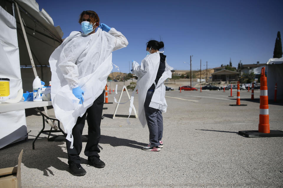 FILE - In this Oct. 26, 2020, file photo, Jacob Newberry puts on new PPE at the COVID-19 state drive-thru testing location at UTEP in El Paso, Texas. As the coronavirus pandemic surges across the nation and infections and hospitalizations rise, medical administrators are scrambling to find enough nursing help — especially in rural areas and at small hospitals. (Briana Sanchez/The El Paso Times via AP, File)