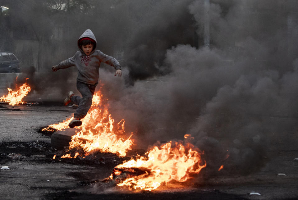 A boy jumps over burning tires that were set on fire to block a road, during a protest in Beirut, Lebanon, Tuesday, March 2, 2021. Scattered protests broke out in different parts of Lebanon Tuesday after the Lebanese pound hit a record low against the dollar on the black market, a sign of the country's multiple crises deepening with no prospects for a new Cabinet in the near future. (AP Photo/Hassan Ammar)