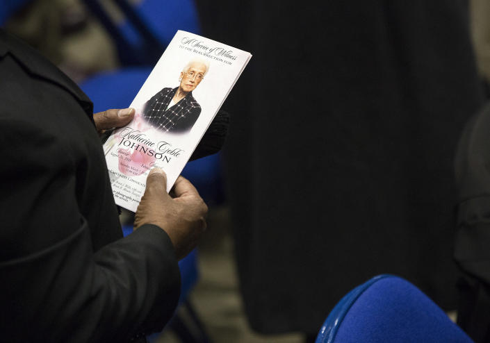 """A guest holds a program during a memorial service to honor NASA mathematician Katherine Johnson on Saturday, March 7, 2020, at Hampton University Convocation Center in Hampton, Va. Johnson, a mathematician who calculated rocket trajectories and earth orbits for NASA's early space missions and was later portrayed in the 2016 hit film """"Hidden Figures,"""" about pioneering black female aerospace workers died on Monday, Feb. 24, 2020. She was 101. (Kaitlin McKeown /The Virginian-Pilot via AP)"""