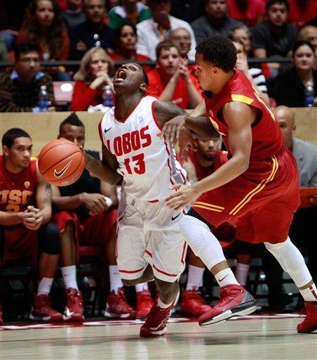 New Mexico's Jamal Fenton, left, collides with Southern California's Chass Bryan in the first half of an NCAA college basketball game at The Pit in Albuquerque, N.M. Wednesday, Dec. 5, 2012. New Mexico won 75-67. (AP Photo/Eric Draper)