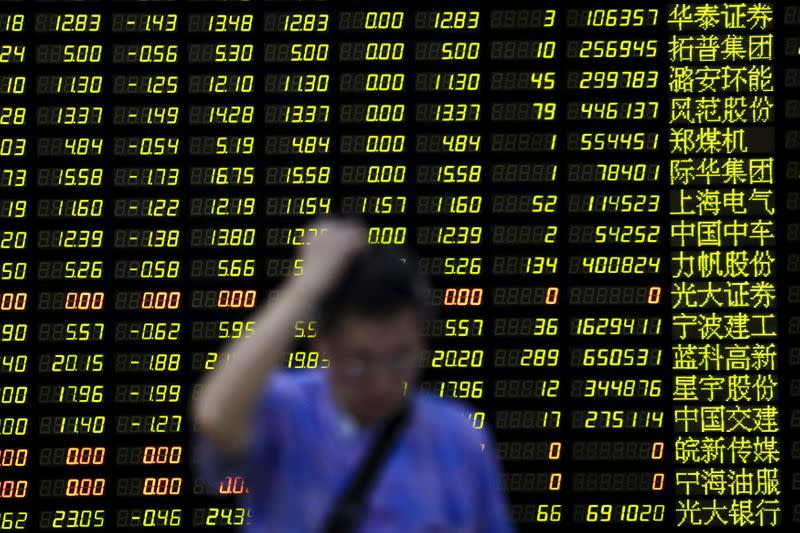 FILE PHOTO: An investor stands in front of electronic board showing stock information at brokerage house in Shanghai