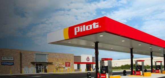 Gas station awning with Pilot logo on it, in front of storefront.