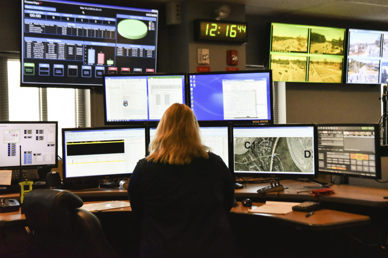 FILE - In this March 15, 2018, file photo, a dispatcher works at a desk station with a variety of screens used by those who take 911 emergency calls. Jobs with state and city governments are usually a source of stability in the U.S. economy, but the financial devastation wrought by the coronavirus pandemic has forced cuts that will reduce public services, from schools to trash pickup. In some areas, 911 calls are taking a longer time to be answered. (AP Photo/Lisa Marie Pane, File)