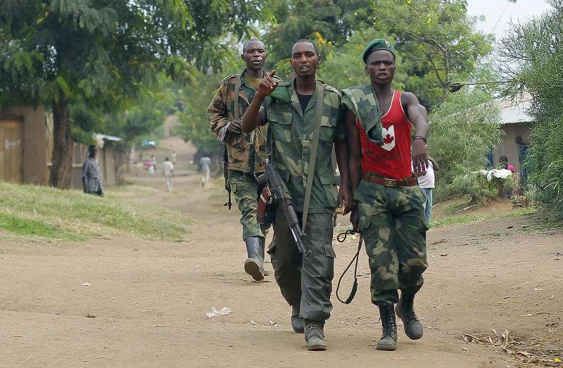 FILE - In this Aug. 5, 2012 file photo, M23 rebel fighters walk through the streets of Kiwanja 80 kilometers (50 miles) north of Goma, Congo. A Rwandan-backed rebel group advanced to within 3 kilometers (1.8 miles) of Goma on Sunday, Nov. 18, 2012, a crucial provincial capital in eastern Congo, marking the first time that rebels have come this close since 2008. (AP Photo/Jerome Delay, File)
