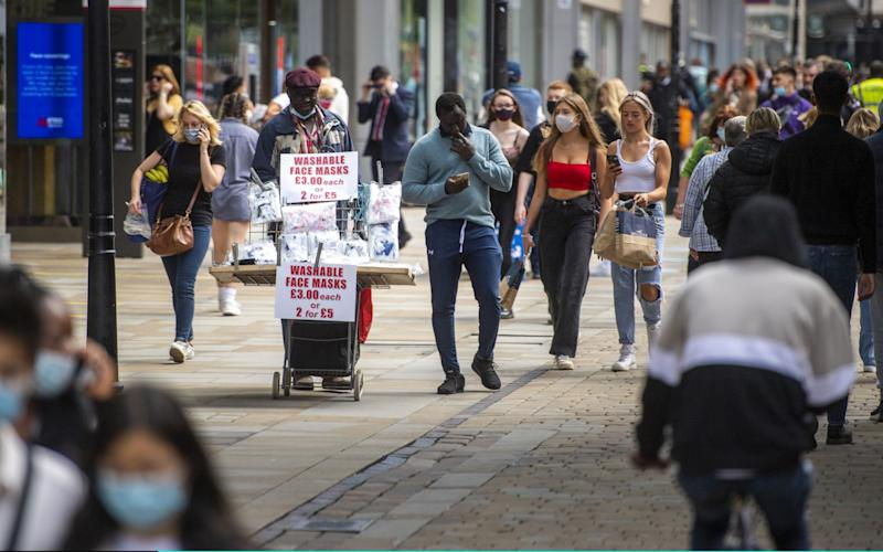 A street vendor sells face masks on Market Street in Manchester, as people from different households in Greater Manchester, parts of East Lancashire and parts of West Yorkshire are banned from meeting each other indoors from midnight - Anthony Devlin/Getty