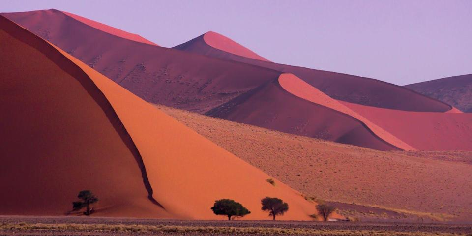 """<p>Located in the southern portion of the Namib Desert, the <a href=""""https://www.tripadvisor.com/Attraction_Review-g479221-d480625-Reviews-Sossusvlei-Namib_Naukluft_Park_Khomas_Region.html"""" rel=""""nofollow noopener"""" target=""""_blank"""" data-ylk=""""slk:Sossusvlei"""" class=""""link rapid-noclick-resp"""">Sossusvlei</a> sand dunes are some of the largest on Earth. These massive rust-hued sand mounds are simply stunning to see in person — but visitors don't just look at them, they get to climb on them as well! Sunrise and sunset, when the arid landscape is awash in shades of red, and orange, are peak climbing times. </p>"""