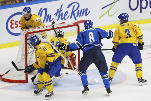 Finland's Saku Maenlanen (8) reacts after scoring on Sweden's goalie Oscar Dansk as Sweden's Filip Sandberg (L) and Robin Norell (R) watch the puck during the second period of their IIHF World Junior Championship gold medal ice hockey game in Malmo, Sweden, January 5, 2014. REUTERS/Alexander Demianchuk (SWEDEN - Tags: SPORT ICE HOCKEY)