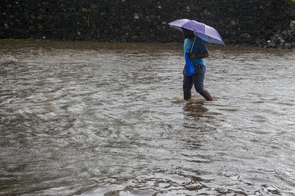 A boy wades through a flooded during a heavy monsoon rain in Mumbai on August 4, 2020. (Photo by INDRANIL MUKHERJEE/AFP via Getty Images)