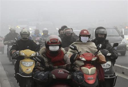 Residents wearing masks ride their electric bicycles on a street amid heavy haze in Shaoxing, Zhejiang province