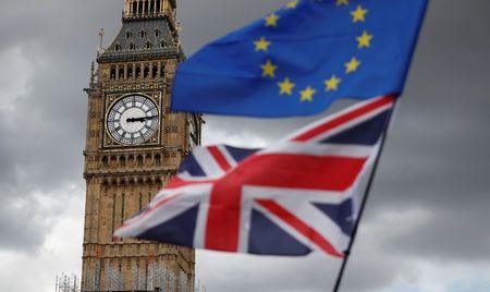 The Union Flag and a European Union flag fly near the Elizabeth Tower, housing the Big Ben bell, during the anti-Brexit 'People's March for Europe', in Parliament Square in central London