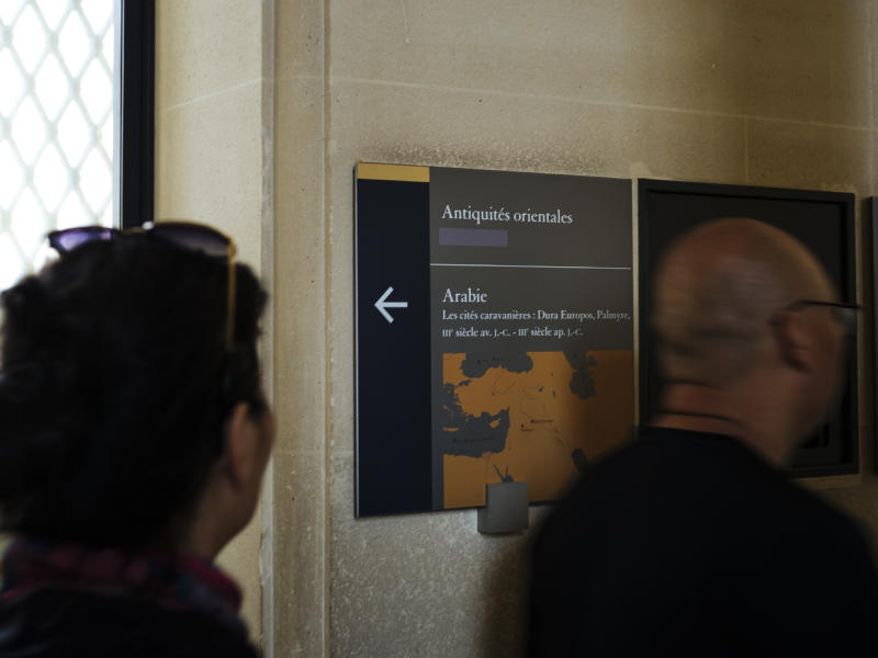 Visiotrs walk past a taped over sign at the Louvre Museum in Paris, France, Wednesday, July 17, 2019. France's Louvre museum has taped over the Sackler name as donors to a wing of the building after protests against the family blamed for the opioid crisis in the United States. (AP Photo/Kamil Zihnioglu)