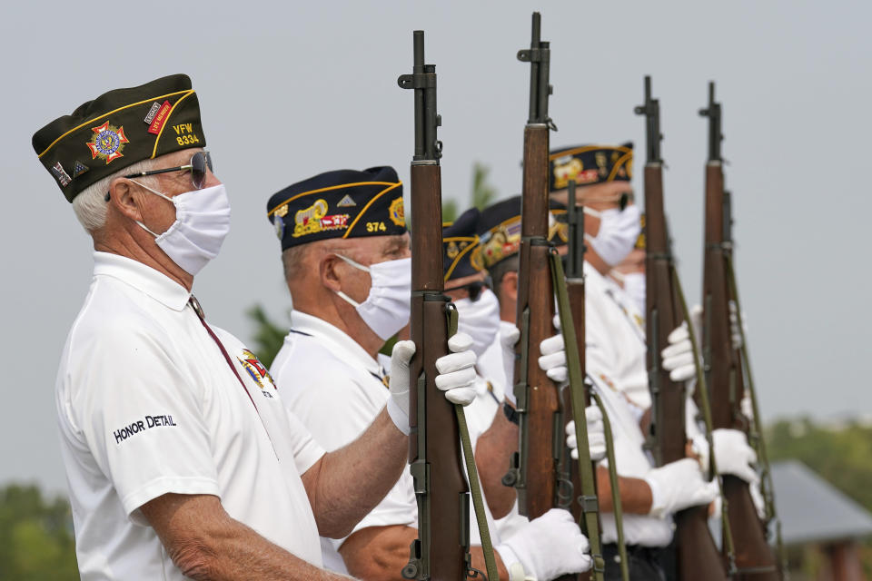 An honor guard with the American Legion Post 374 of Millard wear face masks against COVID-19 present arms during the graveside service of David Owen Cary at the Omaha National Cemetery in Omaha, Neb., Thursday, Sept. 17, 2020. (AP Photo/Nati Harnik)