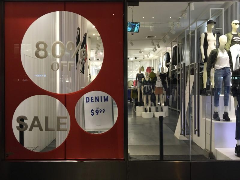 An H&M store has sale signs in the window in New York City