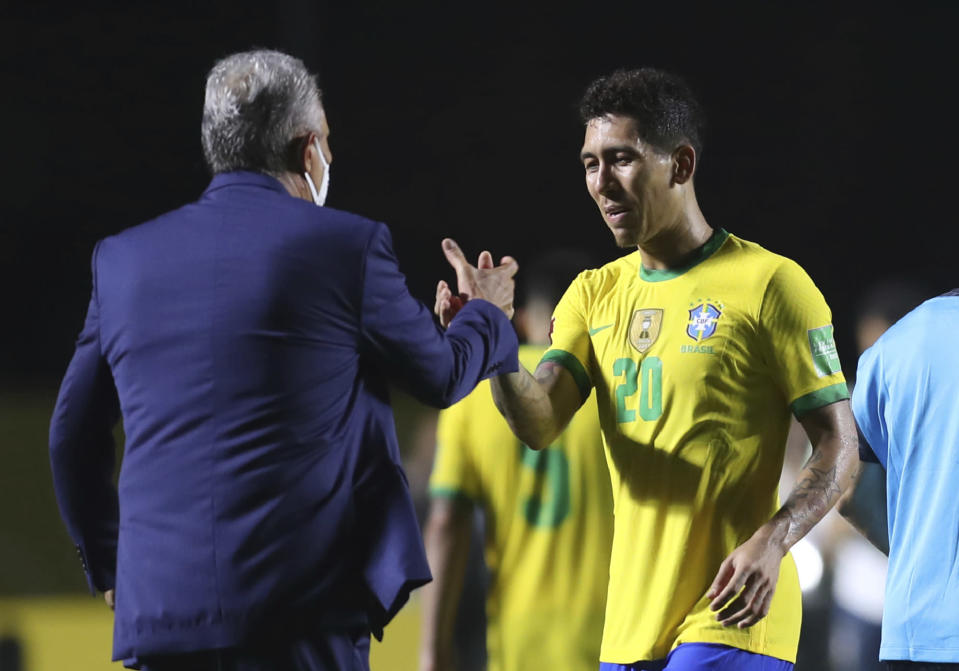 Brazil's coach Tite, left, and Brazil's Roberto Firmino celebrate at the end of a qualifying soccer match against Venezuela for the FIFA World Cup Qatar 2022 in Sao Paulo, Brazil, Friday, Nov.13, 2020. Brazil won 1-0. (Fernando Bizerra/Pool via AP)