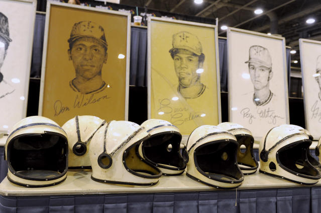 Space helmets worn by the grounds crew in the early years of the Houston Astrodome are lined up in front of drawings of former Houston Astros players on Saturday, Nov. 2, 2013, at the Reliant Center in Houston. A sale and auction of Houston Astrodome furniture, appliances, Astroturf and staff uniforms was held Saturday. The Astrodome was the world's first multipurpose domed stadium and was once home to the Astros and the Oilers. The stadium has been closed to all events since 2009. (AP Photo/Pat Sullivan)