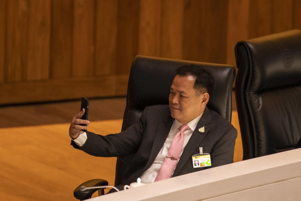Thailand's Public Health Minister Anutin Charnvirakul takes a selfie before the start of a no-confidence debate at the parliament in Bangkok, Thailand, Tuesday, Feb. 16, 2021. The opposition parties are targeting 10 Cabinet​ ministers with allegations ranging from poor management to corruption. (AP Photo/Sakchai Lalit)