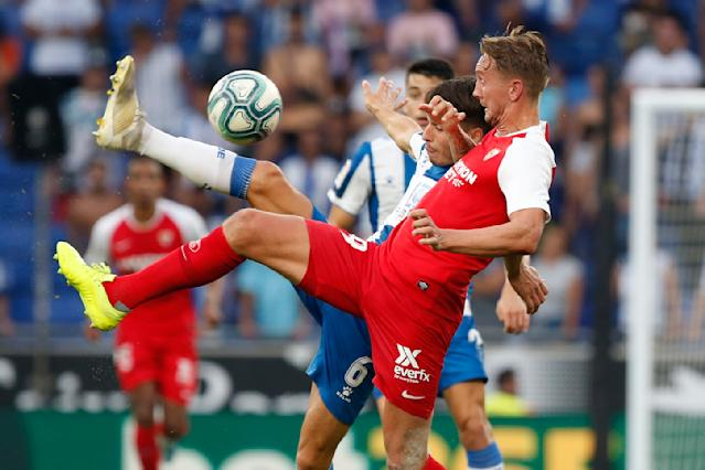 Sevilla's Luuk de Jong, foreground and Espanyol's Lluis Lopez challenges for the ball during the Spanish La Liga soccer match between Espanyol and Sevilla at the RCDE Stadium in Barcelona, Spain, Sunday Aug.18, 2019. (AP Photo/Joan Monfort)