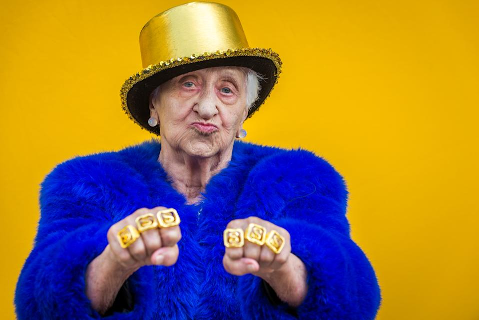 Old woman wearing gold hat and gold rings posing and looking rich.