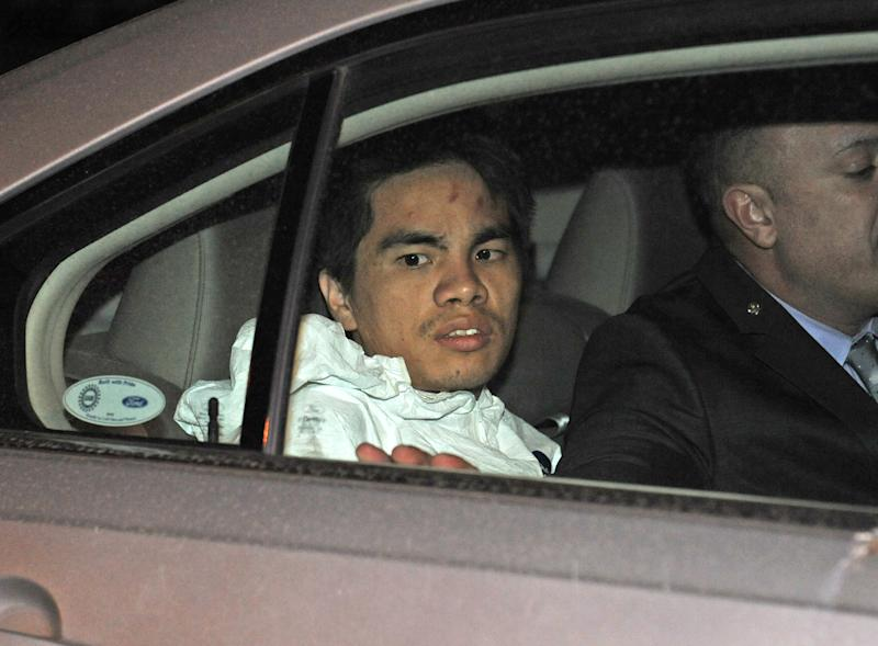 Mingdong Chen, a suspect in the murder of a five people in Brooklyn's Sunset Park neighborhood, is taken by police from the 66th precinct, Sunday, Oct. 27, 2013 in New York. The Chinese immigrant, who neighbors said struggled to survive in America, was arrested in the stabbing death Saturday night of his cousin's wife and her four children. (AP Photo/ Louis Lanzano)