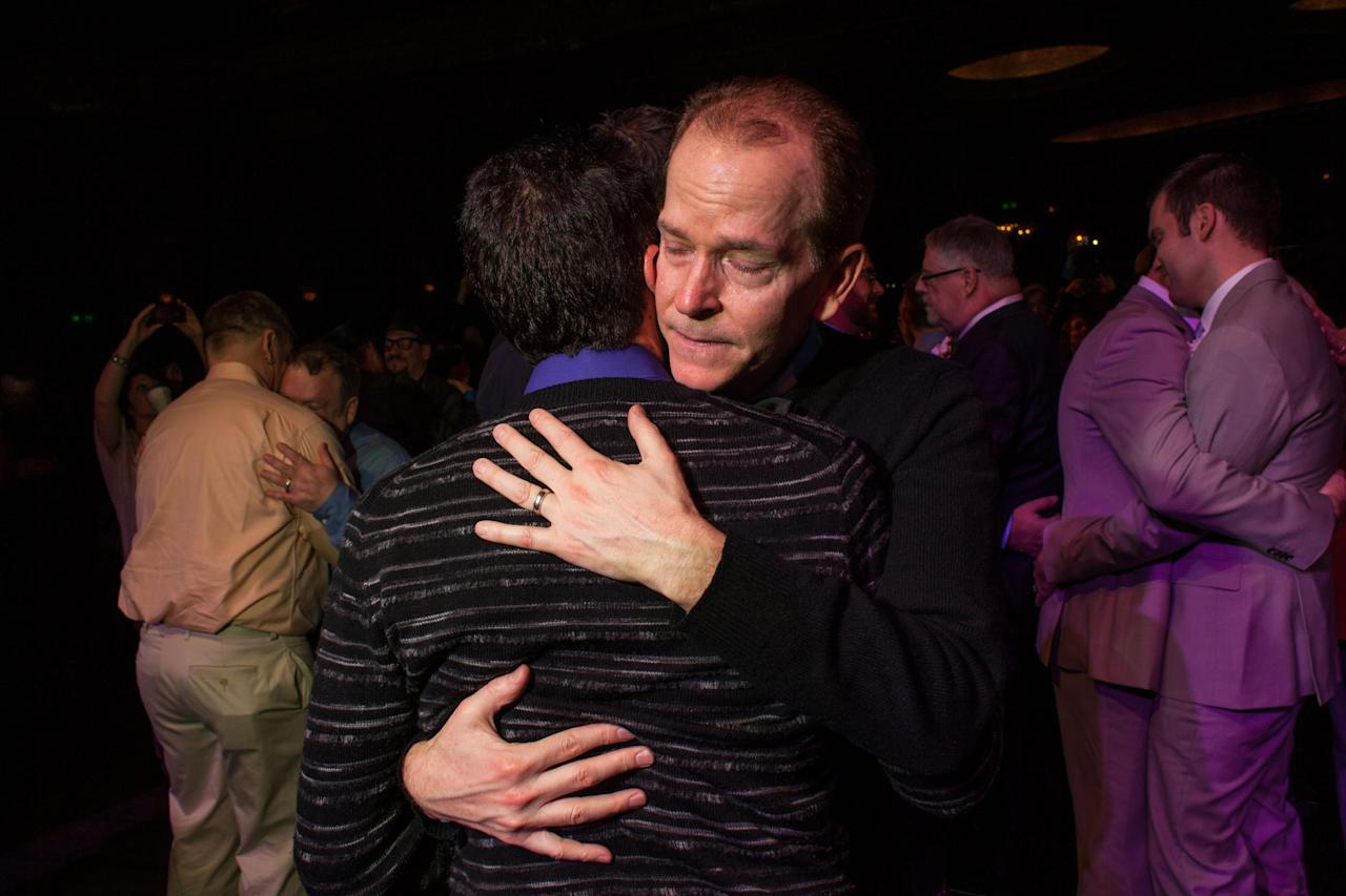 "SEATTLE, WA - DECEMBER 9: Steve Rubio shares an emotional first dance with his husband Sonny Feldman during ""A Wedding Reception for All,"" which was attended by hundreds and held at the Paramount Theatre on December 9, 2012 in Seattle, Washington. Today is the first day that same-sex couples can legally wed in Washington state. (Photo by David Ryder/Getty Images)"