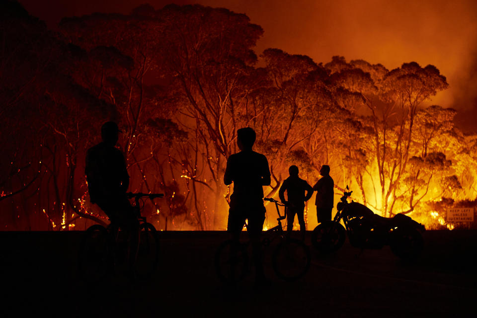 Residents look on as flames burn through bush in Lake Tabourie, Australia.