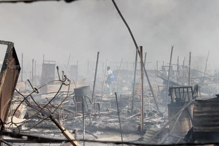 People walk among rubble in an United Nations base in the northeastern town of Malakal on February 18, 2016 (AFP Photo/Justin Lynch)