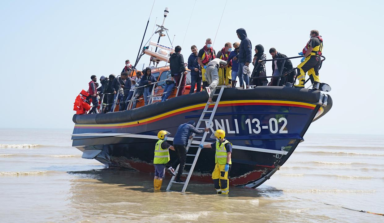 A group of people thought to be migrants crossing from France come ashore from the local lifeboat at Dungeness in Kent, after being picked-up following a small boat incident in the Channel. Picture date: Tuesday July 20, 2021.