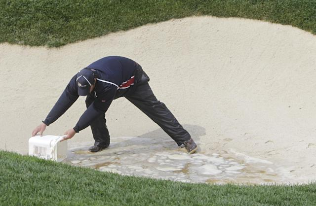A groundskeeper bails water from a bunker on the 15th during a rain delay in the four-ball matches at the Presidents Cup golf tournament at Muirfield Village Golf Club Saturday, Oct. 5, 2013, in Dublin, Ohio. (AP Photo/Jay LaPrete)