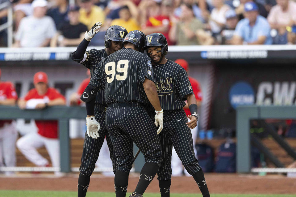 Vanderbilt's Jayson Gonzalez (99), center, celebrates with Enrique Bradfield Jr., left, and Javier Vaz, right, after hitting a two-run home run against Arizona in the fourth inning during a baseball game in the College World Series, Saturday, June 19, 2021, at TD Ameritrade Park in Omaha, Neb. (AP Photo/Rebecca S. Gratz)