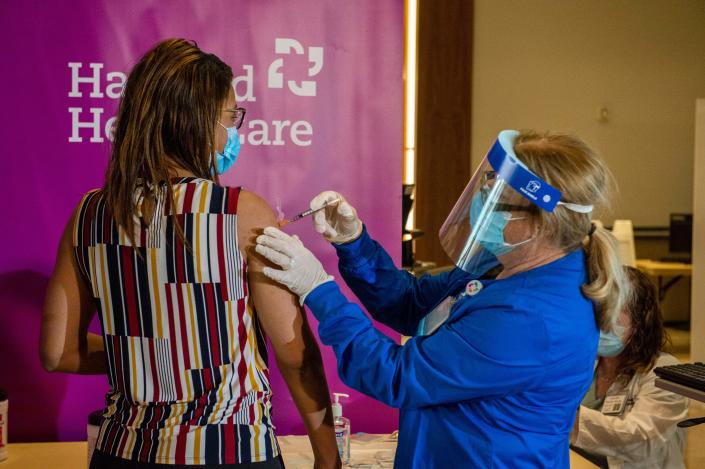 Dr. Melisha Cumberland is given the the second dose of the Pfizer/BioNTech vaccine twenty-one days after receiving the first shot from RN Valerie Massaro of Hartford HealthCare, at the Hartford Convention Center in Hartford, Connecticut on January 4, 2021.(Joseph Prezioso/AFP via Getty Images)