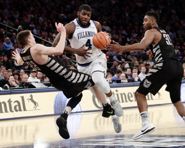 "Villanova's <a class=""link rapid-noclick-resp"" href=""/ncaab/players/126471/"" data-ylk=""slk:Eric Paschall"">Eric Paschall</a> (4) drives past <a class=""link rapid-noclick-resp"" href=""/ncaab/players/131218/"" data-ylk=""slk:Sean McDermott"">Sean McDermott</a> (22) and <a class=""link rapid-noclick-resp"" href=""/ncaab/players/126230/"" data-ylk=""slk:Kelan Martin"">Kelan Martin</a> (30) during the first half of an NCAA college basketball game in the Big East men's tournament semifinals Friday, March 9, 2018, in New York. (AP Photo/Frank Franklin II)"