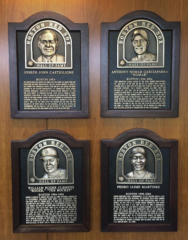 Plaques for 2014 Boston Red Sox Hall of Fame inductees hang at Fenway Park Thursday, Aug. 14, 2014 in Boston. Clockwise from top left are plaques honoring broadcaster Joe Castiglione, shortstop Nomar Garciaparra, pitcher Pedro Martinez and pitcher Roger Clemens. The four men will be honored before Thurday night's game against the Houston Astros. (AP Photo/Jimmy Golen)