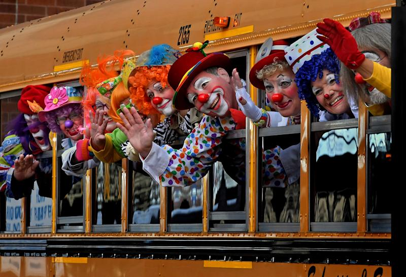 MINNEAPOLIS, MN -MAR 16: A group of convention attendees wave to fellow clowns that were taking their photo. The group was en route to visit a veterans home. -Nearly 250 clowns came to Minneapolis, Minnesota for the annual World Clown Convention. The event featured seminars on everything from business practices to juggling. The convention comes at a time when the clown business had been dealt several optics set-backs due to pop culture imagery that often depicts clowns as scary or evil. (Photo by Michael S. Williamson/The Washington Post via Getty Images)