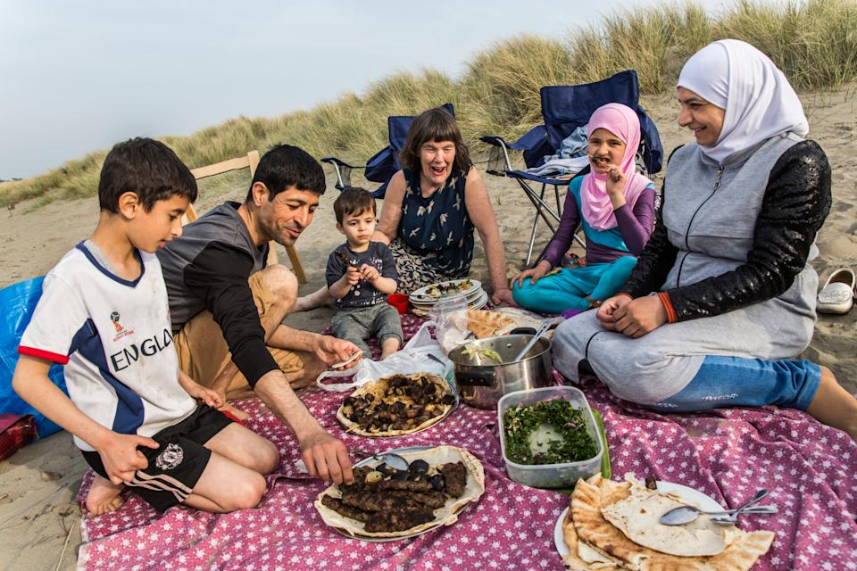 <p>Vicky Moller (centre) has a picnic at a beach in south Wales with the Alchik family, Muhaned, his wife Naheda, and their children (from left) Shadi, 8, Hadi, 1, and Sara, 9, who fled their home during the war in Syria</p>Andrew McConnel