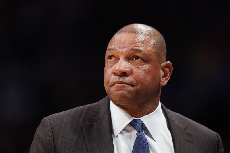 Doc Rivers, in a suit, looks solemn in front of a black background.