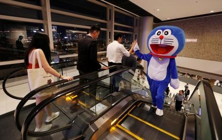 A man wearing a Doraemon mascot costume gives high five to a man during a protest at International Finance Center (IFC) in Hong Kong