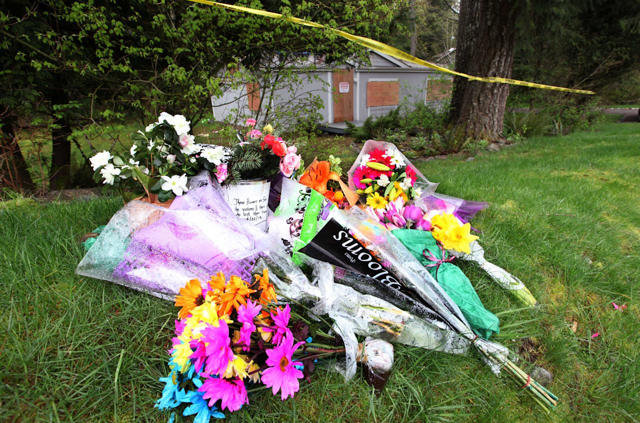 Flowers sit as a make-shift shrine outside the burned-out home where a gun-toting survivalist is suspected of killing his wife and daughter several days earlier Friday, April 27, 2012, in North Bend, Wash. Peter Alex Keller may be holed up in a self-made fort not far from where Seattle's outer suburbs give way to the vast recreational playground of Cascade Mountains. Police expect more people to hit the nearby trails this weekend, and deputies are warning them to steer clear of Keller if they think they see him. (AP Photo/Elaine Thompson)