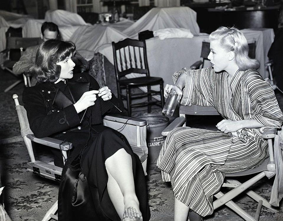 <p>Katharine Hepburn and Ginger Rogers chat (and in Hepburn's case, knits!) on the movie set of Stage Door while waiting for their cue. </p>