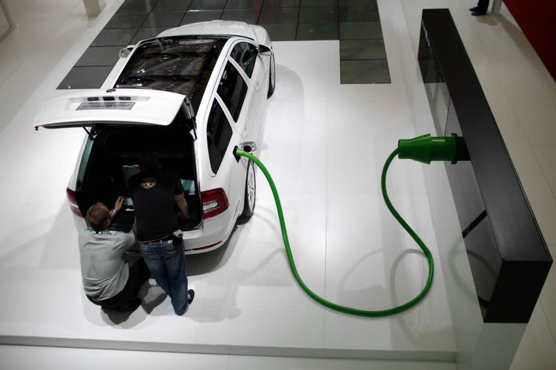 Men work on a Skoda Green E Line car during the 14th Shanghai International Automobile Industry Exhibition
