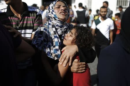 A Palestinian mother comforts her child after what medics said was an Israeli shell that hit a U.N-run school sheltering Palestinian refugees, at a hospital in Jabaliya in the northern Gaza Strip