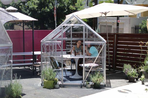PHOTO: Nuria Bosch, 29, and Dria Abramson, 29, eat lunch in a social distancing greenhouse dining pod set up in the former parking lot of the Lady Byrd Cafe in Los Angeles, July 7, 2020. (Lucy Nicholson/Reuters)