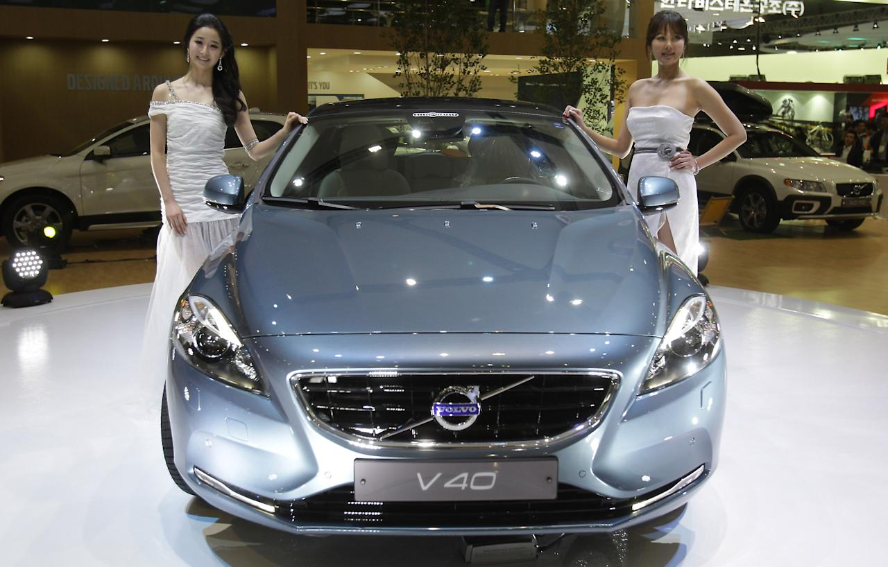 GOYANG, SOUTH KOREA - MARCH 28:  Models pose next to a Volvo V40 at the Seoul Motor Show 2013 on March 28, 2013 in Goyang, South Korea. The Seoul Motor Show 2013 will be held in March 29-April 7, featuring state-of-the-art technologies and concept cars from global automakers. The show is its ninth since the first one was held in 1995. About 384 companies from 14 countries, including auto parts manufacturers and tire makers, will set up booths to showcase trends in their respective industries, and to promote their latest products during the show.  (Photo by Chung Sung-Jun/Getty Images)