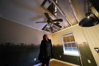A warped ceiling fan hangs near a hole in the roof of Dewana Young's heavily damaged home, in the aftermath of both Hurricane Laura and Hurricane Delta, in Grand Lake, La., Friday, Dec. 4, 2020. (AP Photo/Gerald Herbert)