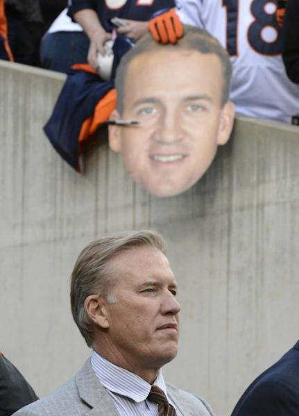 John Elway, executive vice president of football operations for the Denver Broncos, stands on the field as a fan holds a photo of Broncos quarterback Peyton Manning in the background in the second half of an NFL football game against the Cincinnati Bengals, Sunday, Nov. 4, 2012, in Cincinnati. Denver won 31-23. (AP Photo/Michael Keating)