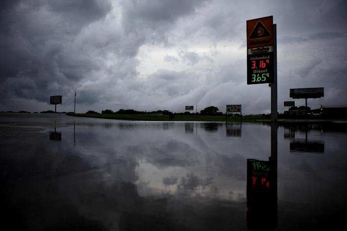 Storm clouds are reflected in the flooded parking lot of a gas station in Level Plains, Ala. after heavy rains moved through the area Sunday, June 10, 2012. (AP Photo/Dothan Eagle, Max Oden)