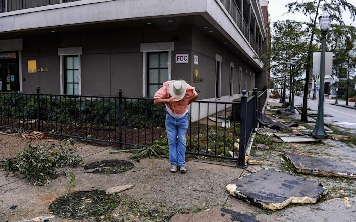 A man in Mobile, Alabama, clings on to his hat in high winds - CHANDAN KHANNA /AFP