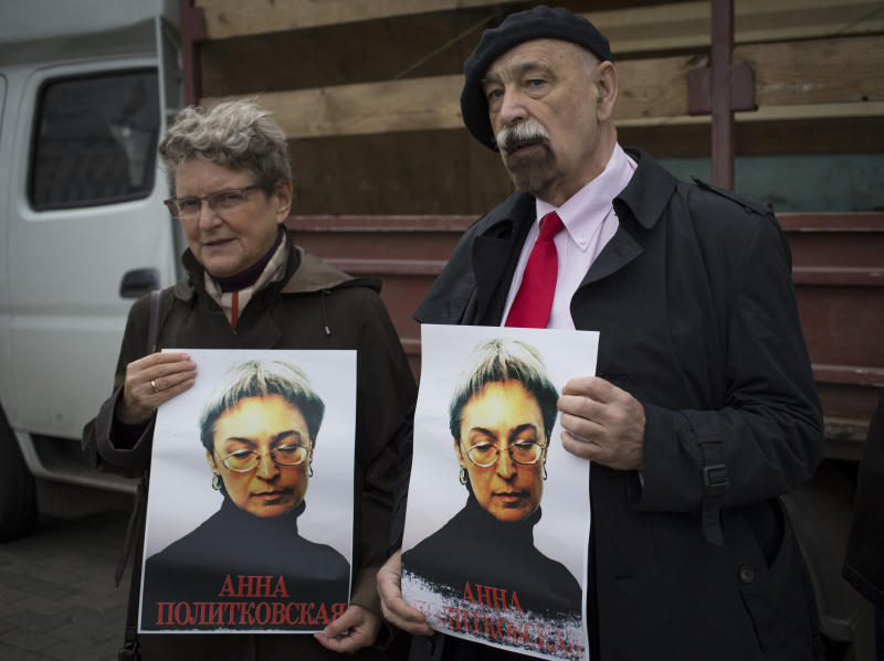 "Svetlana Gannushkina, left, a mathematician and human rights activist and Valery Borshchev, a member of the Board of the All-Russian human rights movement ""For Human Rights"" stand holding portraits of slain journalist Anna Politkovskaya, in downtown Moscow, Sunday, Oct. 7, 2012. About 200 people rallied Thursday on the 6th anniversary of the killing of Anna Politkovskaya, calling on the authorities to find and punish the killers of journalists and human rights activists in Russia. (AP Photo/Alexander Zemlianichenko)"