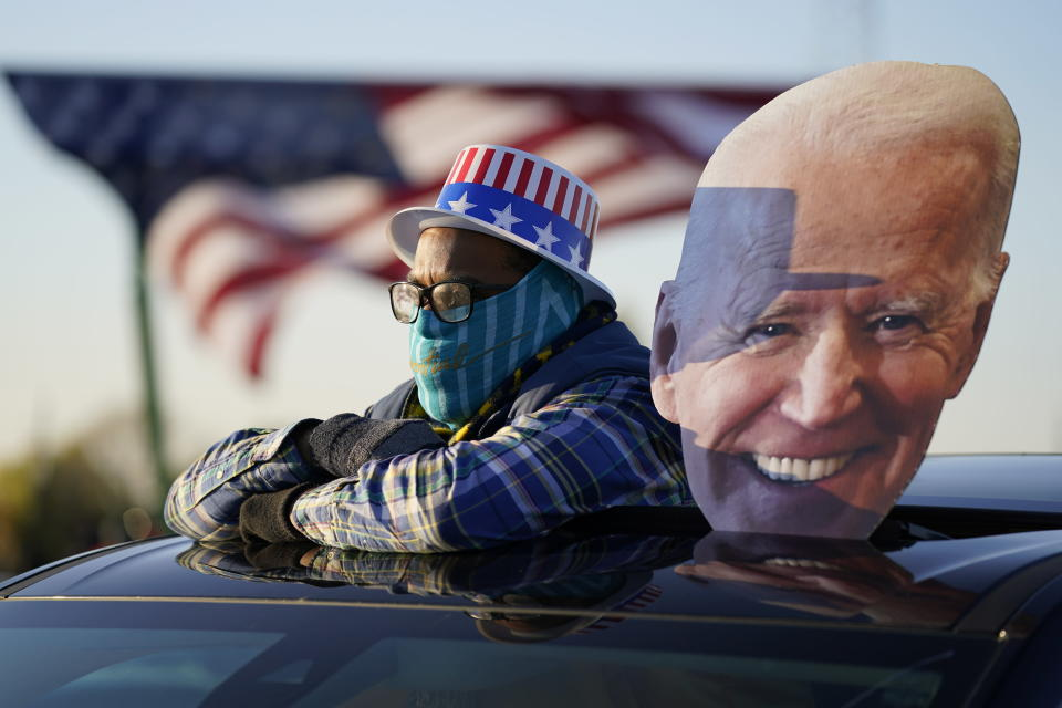 A supporter watches as Democratic presidential candidate former Vice President Joe Biden and former President Barack Obama speak at a rally at Belle Isle Casino in Detroit, Mich., Saturday, Oct. 31, 2020. (AP Photo/Andrew Harnik)