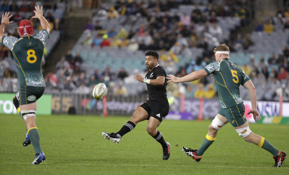 New Zealand's Richie Mo'unga, center, kicks between Australian defenders Harry Wilson, left, and Matt Philip during their Bledisloe rugby test match at Stadium Australia, Sydney, Australia, Saturday, Oct. 31, 2020. (AP Photo/Rick Rycroft)